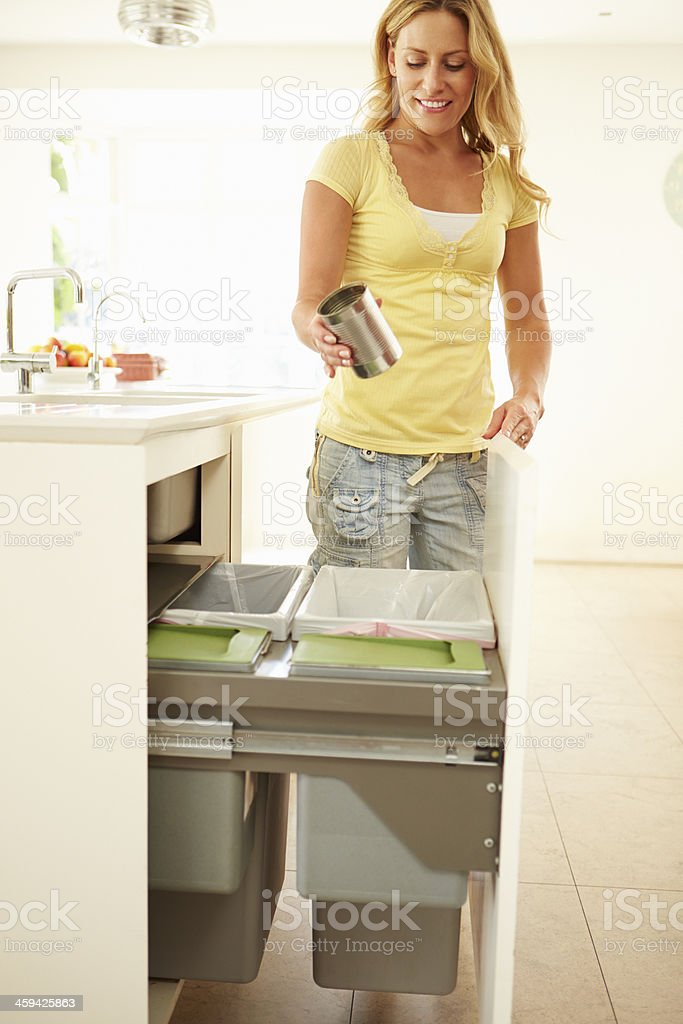 Woman recycling in the kitchen stock photo