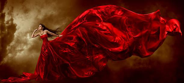 frau in rot winken schönes kleid mit stoff, künstlerische himmel hintergrund - lange abendkleider stock-fotos und bilder