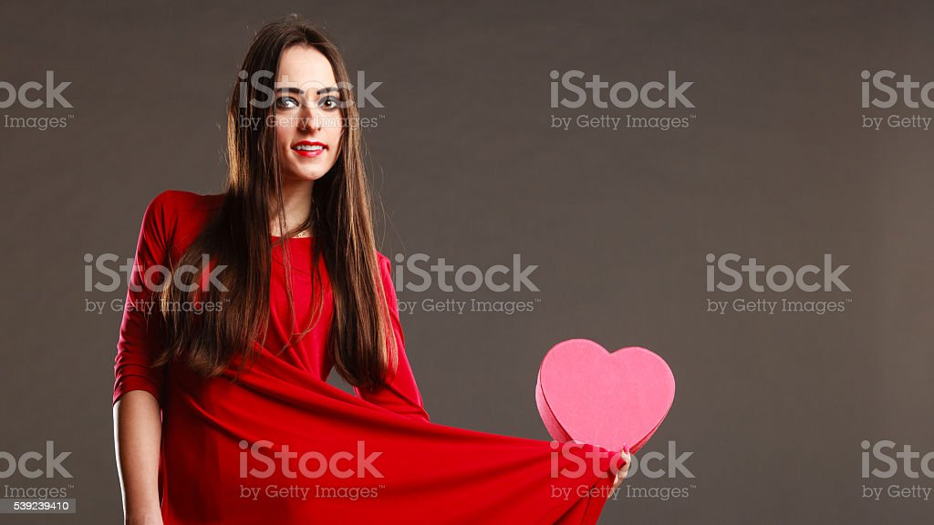 Woman red dress holds heart shaped box royalty-free stock photo