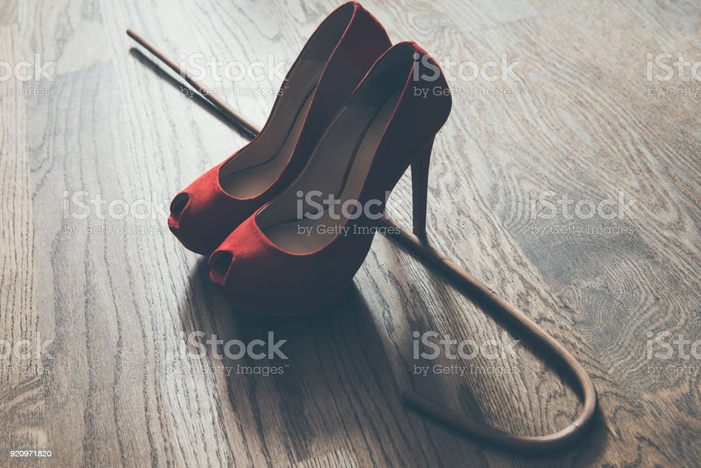 Woman red high heel shoes and rattan school cane. Strict domination bdsm concept. stock photo