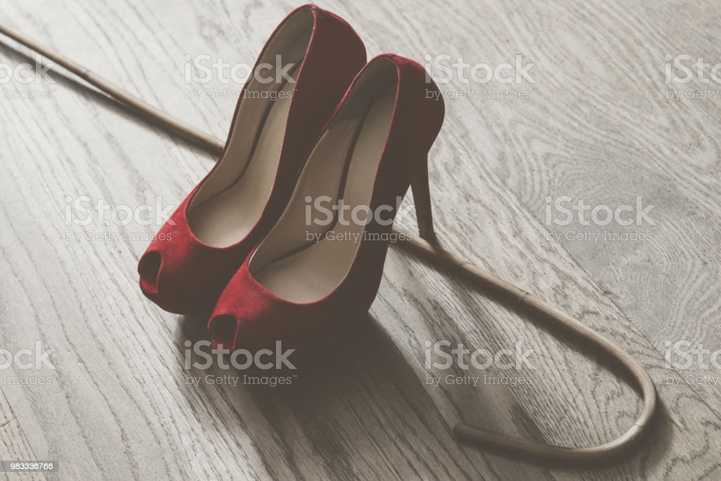 Woman red high heel shoes and rattan school cane. Strict woman domination bdsm concept. adult role game stock photo