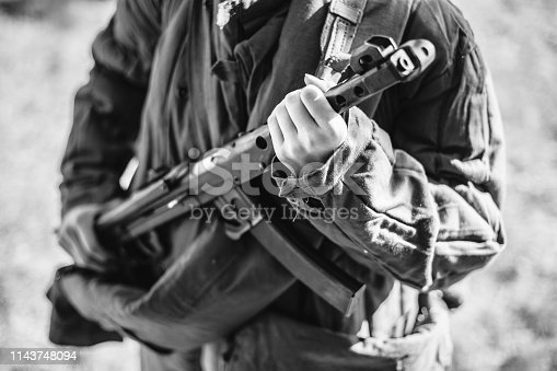 1061204700 istock photo Woman Re-enactor Dressed As World War Ii Soviet Russian Red Army Soldier Holding World War II Weapon Submachine Gun Pps-43. WWII WW2 Russian Ammunition. Photo In Black And White Colors 1143748094