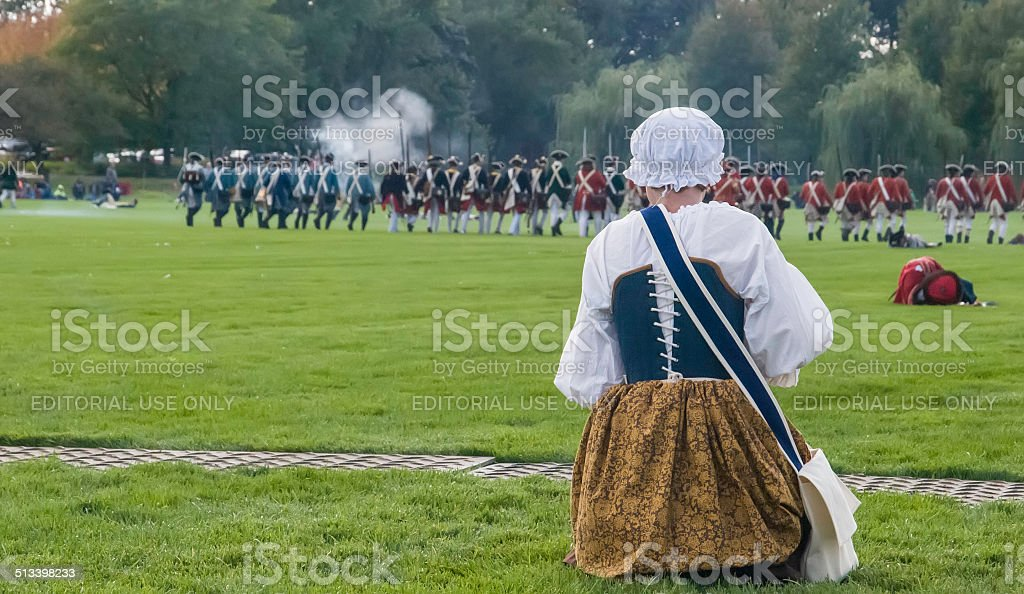 Woman re-enactor in period dress watches a mock battle stock photo
