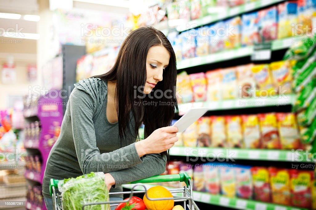 A woman refers to her shopping list while pushing a cart stock photo