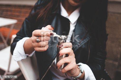 istock Woman refills liquid in e-cigarette closeup. Girl refills liquid in vape. Electronic cigarette concept 1187672148