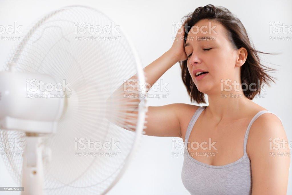 Mujer refrescante frente a un ventilador eléctrico - foto de stock