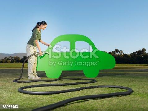 istock Woman refueling cutout car 83266450
