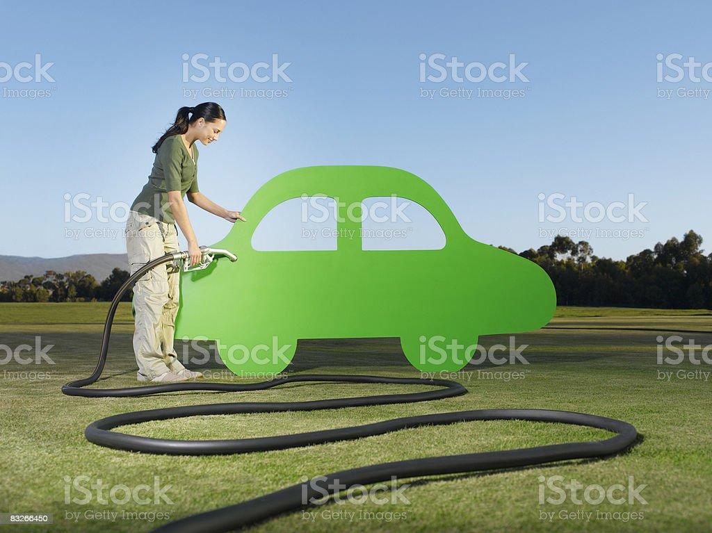 Woman refueling cutout car stock photo