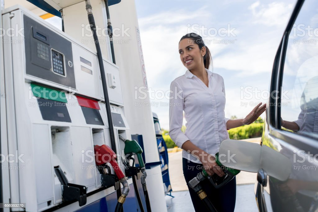Woman refueling her car at a petrol station royalty-free stock photo