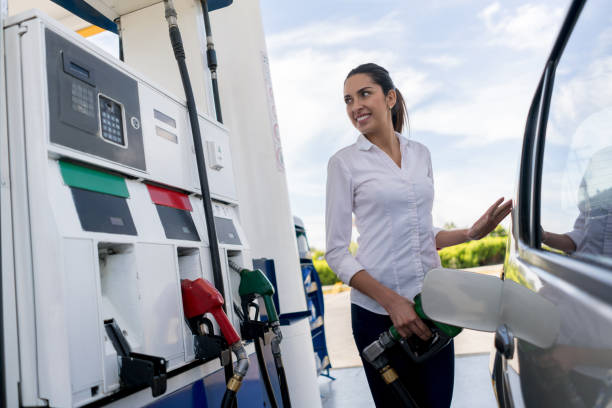 Woman refueling her car at a petrol station stock photo