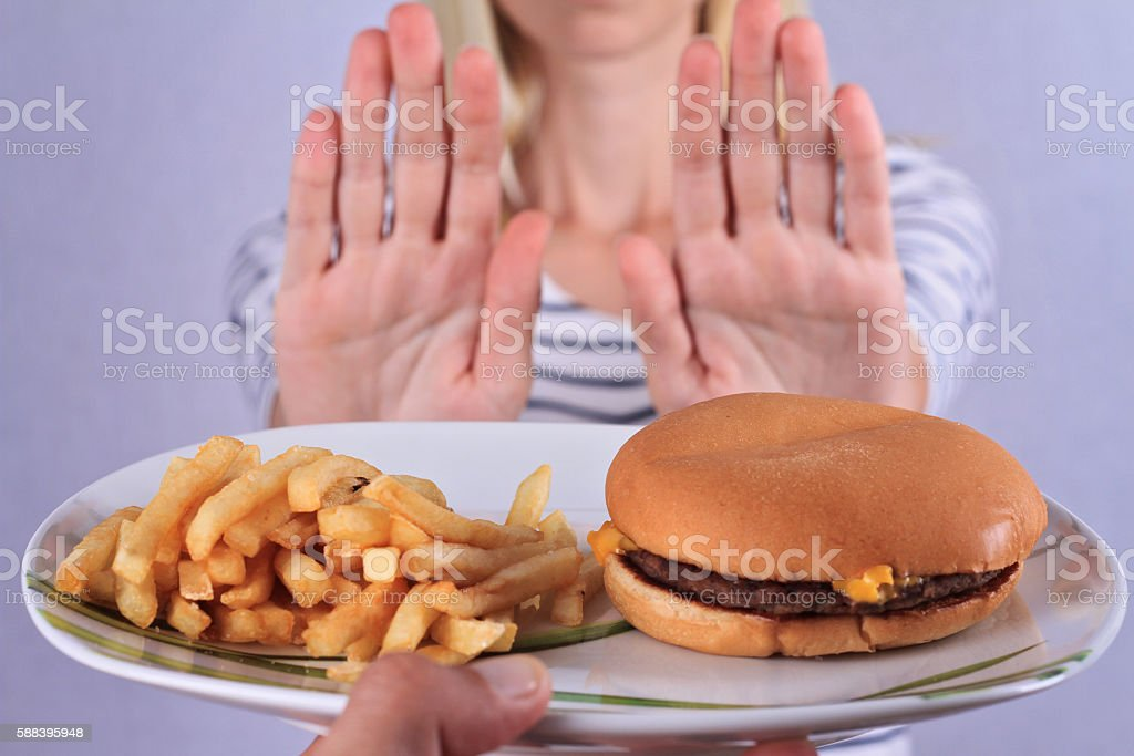 Woman refuses to eat junk food . Woman refuses to eat junk food . Healthy eating and active lifestyle concept Adult Stock Photo