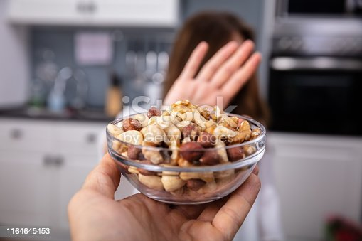 Woman Refusing Bowl Of Nut Food Offered By A Person At Home