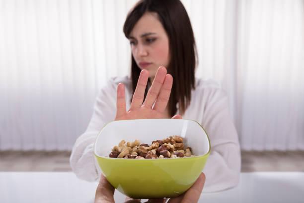 woman refusing nut food - allergie alimentari foto e immagini stock