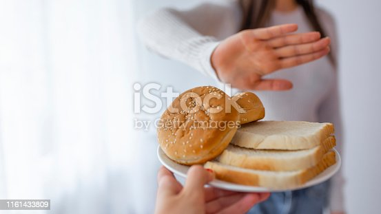 Young woman on gluten free diet is saying no thanks to toast. A woman on a gluten free diet is saying no thanks to toast. Woman refusing to eat white bread