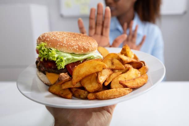 kvinna vägrar ohälsosam mat - matsmältningsbesvär bildbanksfoton och bilder