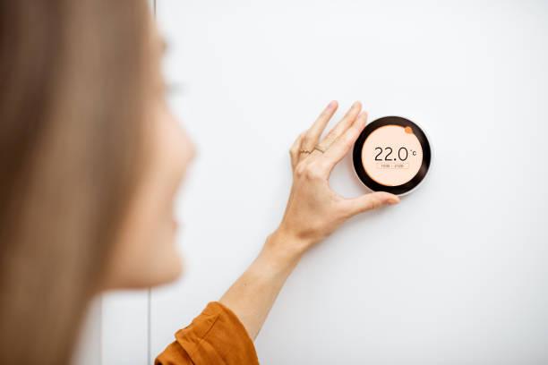 Woman regulating heating temperature at home stock photo