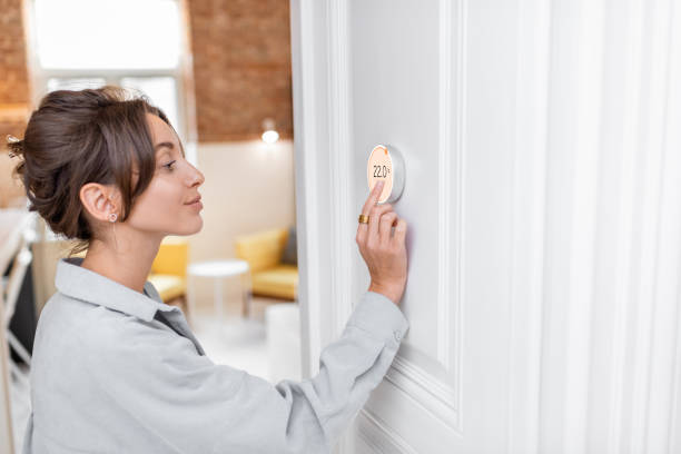Woman regulating heating temperature with a smart thermostat stock photo