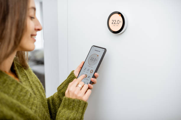 Woman regulating heating temperature with phone and thermostat at home Woman dressed in green sweater regulating heating temperature with a modern wireless thermostat and smart phone at home. Synchronization of thermostat with mobile devices concept home automation stock pictures, royalty-free photos & images