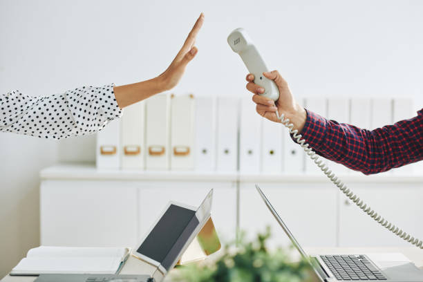 Woman rejecting call in office Crop man outstretching telephone handset to woman showing stop gesture and rejecting to answer call in office ignoring stock pictures, royalty-free photos & images