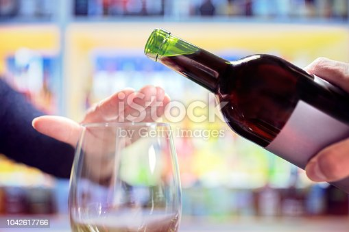 Womans hand rejecting more alcohol from wine bottle in bar