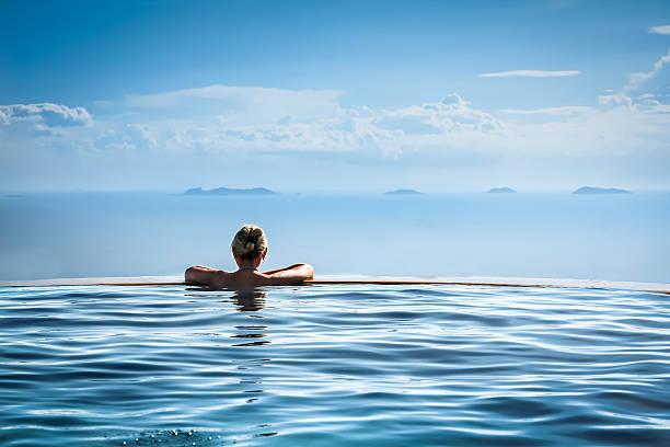 Woman relax in infinity swimming pool on vacation Woman relax and looking into the distance in infinity swimming pool on vacation infinity pool stock pictures, royalty-free photos & images