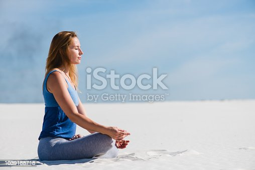 istock Woman relax in lotus yoga pose in desert 1039188718