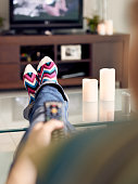 Young caucasian woman laying on sofa with colourful socks. She puts her feet on table and relaxes. The girl watches TV and holds remote control. Focus on socks