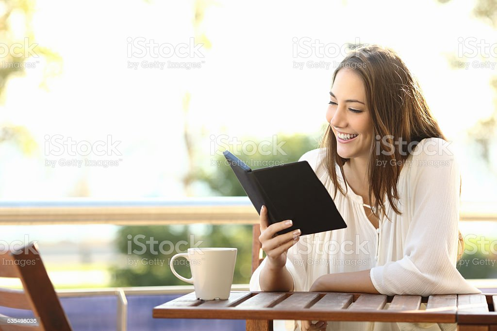 Woman relaxed reading a book in an ebook stock photo