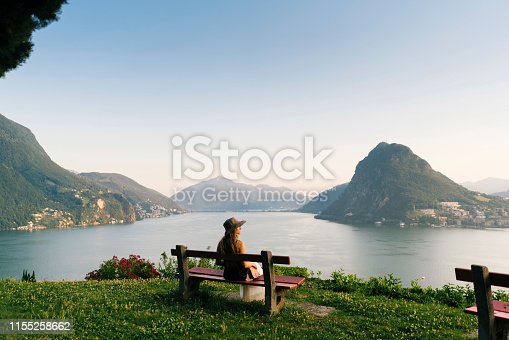 istock Woman relaxes above lake and mountains on bench 1155258662