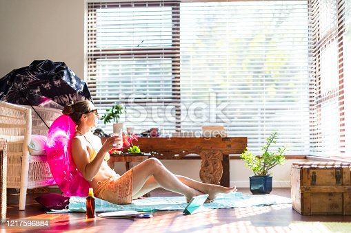 Woman relaxes as if on a summer holiday during COVID-19 travel ban.