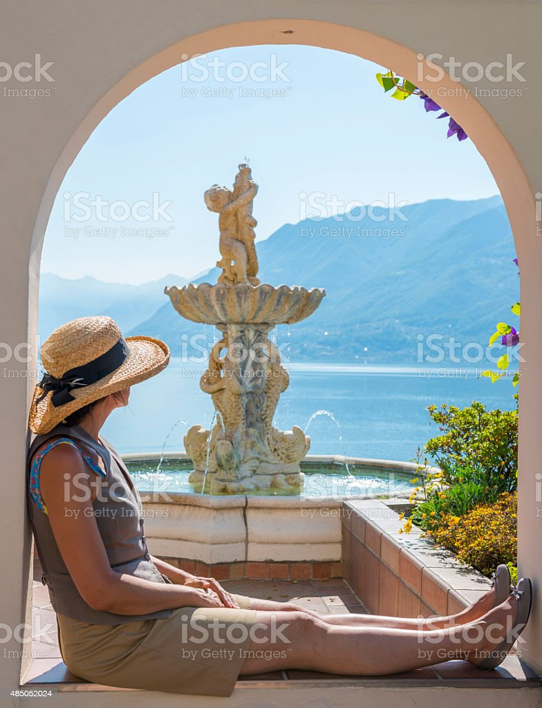 Woman relaxes besides fountain overlooking lake stock photo