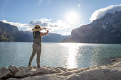 istock Woman relaxes by lakeshore in the morning 1255077003