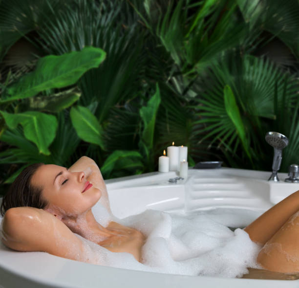 A woman relaxes in hot bath tub with soap foam