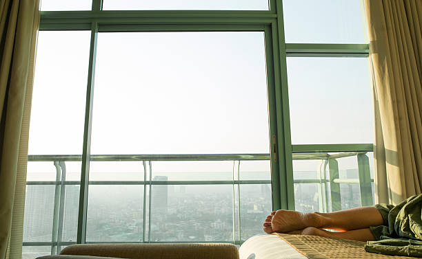 Woman relaxes in hotel room, asleep on bed Woman relaxes in hotel room, asleep on bed,city behind jet lag stock pictures, royalty-free photos & images