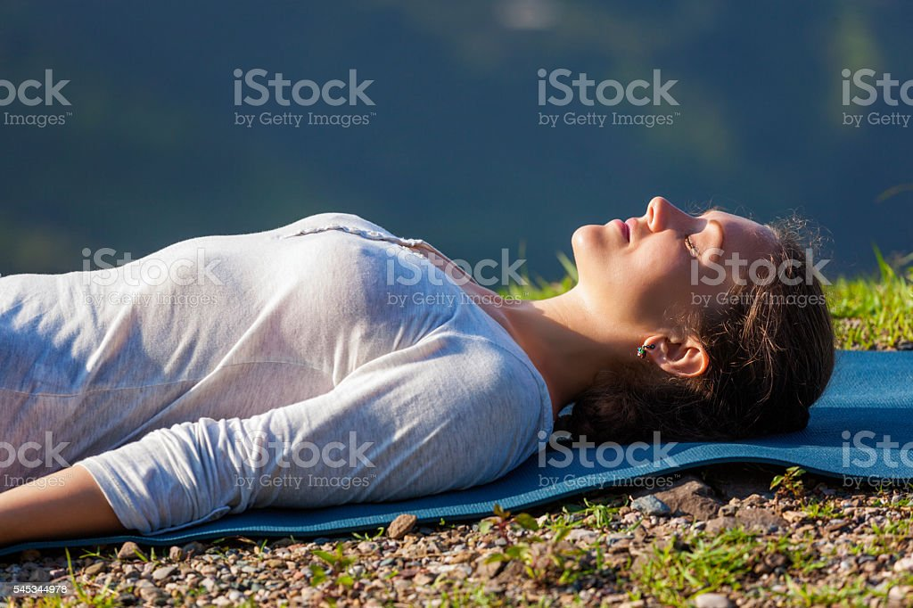 Woman relaxes in yoga asana Savasana outdoors stock photo