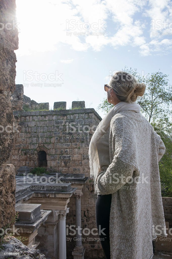 Woman relaxes on castle ramparts, Hadrian's Gate stock photo