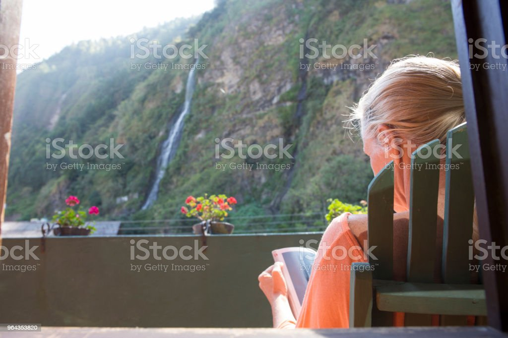 Woman relaxes on elevated deck in front of waterfall stock photo