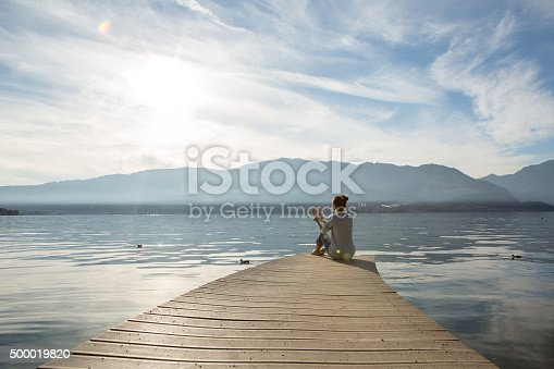 Young woman sits on a jetty above the lake, she is reading a book. Beautiful Autumn day in Italy.
