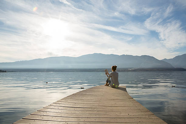 Woman relaxes on lake pier, reads a book stock photo