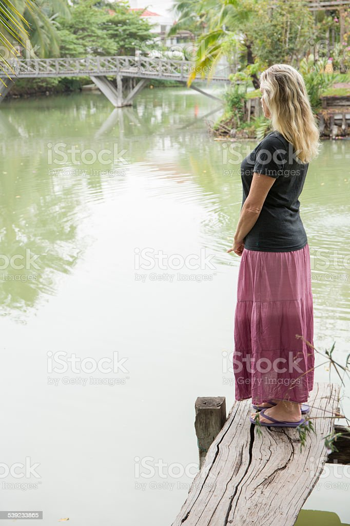 Woman relaxes on lakeside wharf, looking out royalty-free stock photo