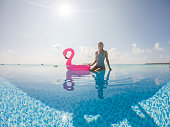 Luxury tropical winter holidays. Woman plays in swimming pool with inflatable flamingo. Maldives