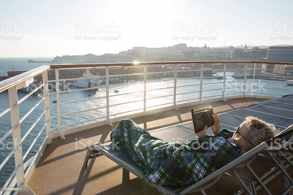 Woman relaxes with digital tablet under blanket stock photo