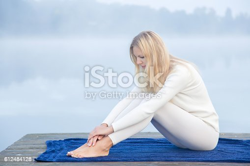 873786782 istock photo Woman relaxing after gymnastics in the mist on the lake. 612484128