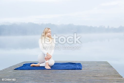 873786782 istock photo Woman relaxing after gymnastics in the mist on the lake. 612484160