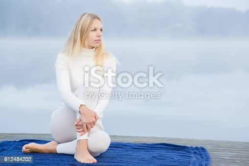 873786782 istock photo Woman relaxing after gymnastics in the mist on the lake. 612484202