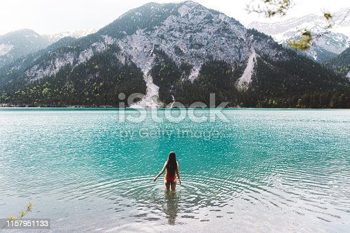 Young woman with long hair and red swimsuit refreshing in cold mountain turquoise colored lake Plan with view of snowcapped mountains in Tyrol, Austria