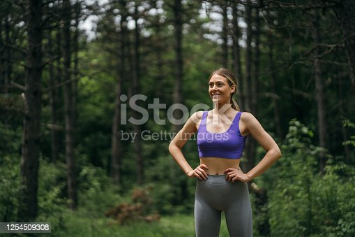 Smiling sports woman relaxing after workout in nature.