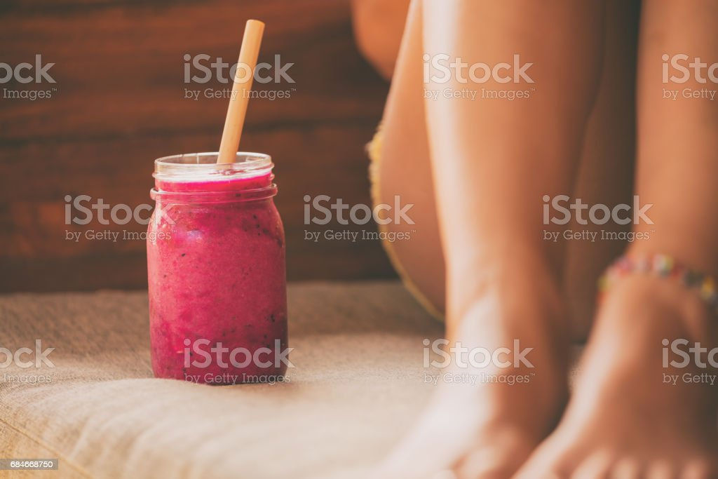 Woman relaxing and drinking smoothie outdoors. stock photo