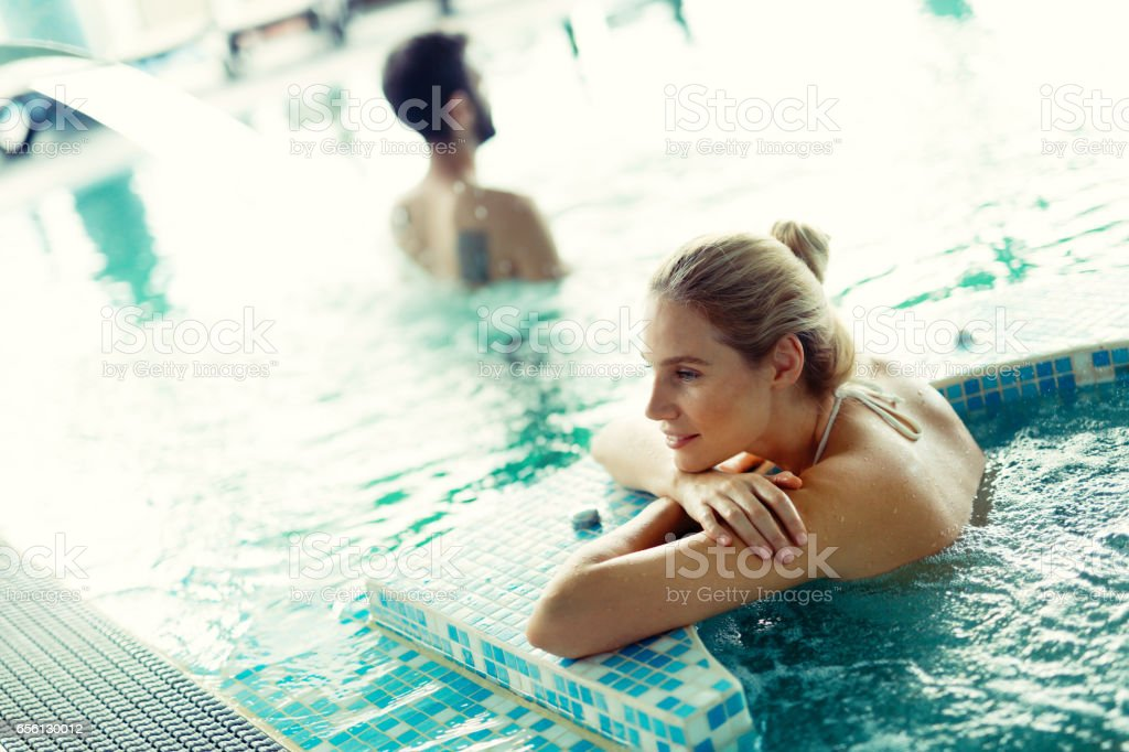 Woman relaxing and enjoying bubble bath in pool and smiling stock photo