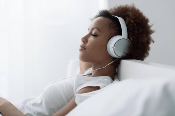 woman relaxing and listening to music - słuchawka nauszna zdjęcia i obrazy z banku zdjęć